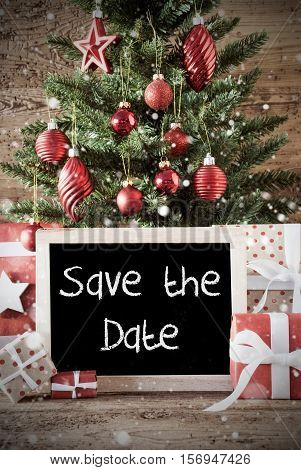 Chalkboard With English Text Save The Date. Nostalgic Christmas Card For Seasons Greetings. Christmas Tree With Balls. Gifts Or Presents In The Front Of Wooden Background.