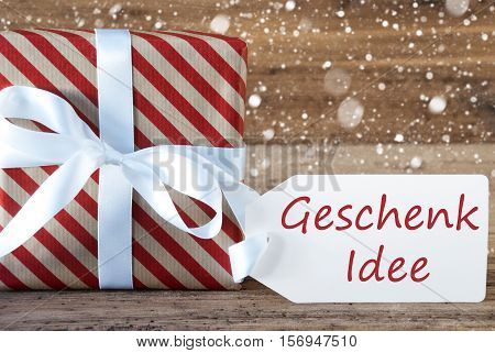 German Text Geschenk Idee Means Gift Idea. Christmas Gift Or Present On Wooden Background With Snowflakes. Card For Seasons Greetings. White Ribbon With Bow.