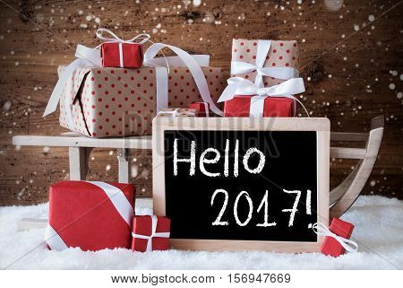 Sled With Christmas And Winter Decoration And Snowflakes. Gifts And Presents On Snow With Wooden Background. Chalkboard With English Text Hello 2017 For Happy New Year