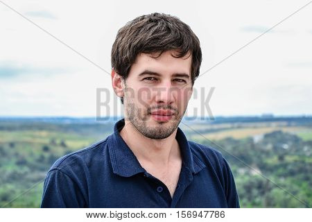 Portrait of serious casual young man standing against natural background