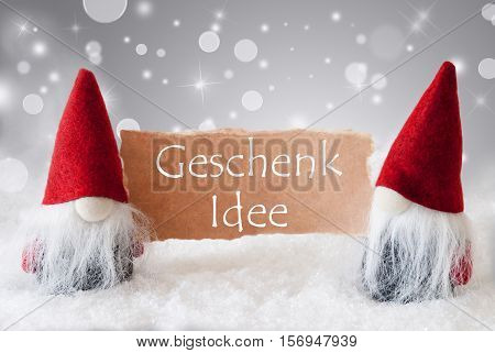 German Text Geschenk Idee Means Gift Idea. Christmas Greeting Card With Two Red Gnomes. Sparkling Bokeh And Noble Silver Background With Snow.