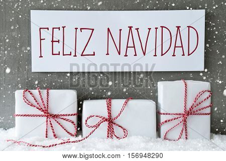 Label With Spanish Text Feliz Navidad Means Merry Christmas. Three Christmas Gifts Or Presents On Snow. Cement Wall As Background With Snowflakes. Modern And Urban Style.