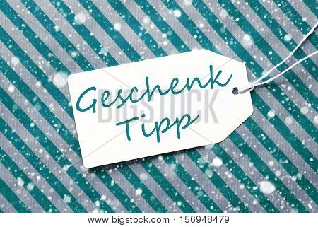 German Text Geschenk Tipp Means Gift Tip. One Label On A Turquoise Striped Wrapping Paper. Textured Background With Snowflakes. Tag With Ribbon.
