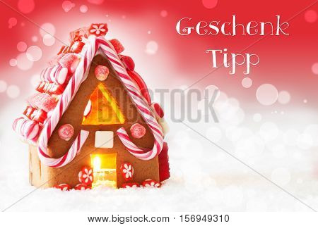 German Text Geschenk Tipp Means Gift Tip. Gingerbread House In Snowy Scenery As Christmas Decoration. Candlelight For Romantic Atmosphere. Red Background With Bokeh Effect.