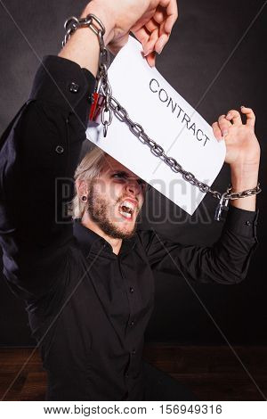 Stress at work no freedom pursuit of money concept. Angry man with chained hands holding contract studio shot on dark grunge background
