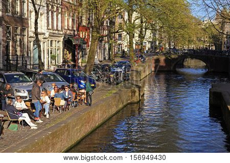 AMSTERDAM, NETHERLANDS - MAY 03, 2016: People relaxing in the sidewalk cafe by a river canal in Amsterdam, Netherlands.