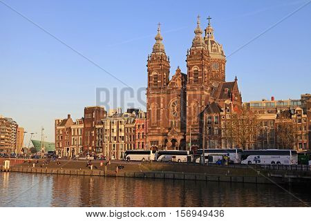 AMSTERDAM, NETHERLANDS - MAY 3, 2016: View of St Nicholas church and houses from across the Amstel River, Amsterdam, Netherlands. Sunset light
