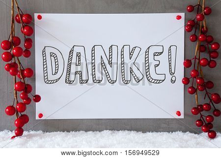 Label With German Text Danke Means Thank You. Red Christmas Decoration On Snow. Urban And Modern Cement Wall As Background