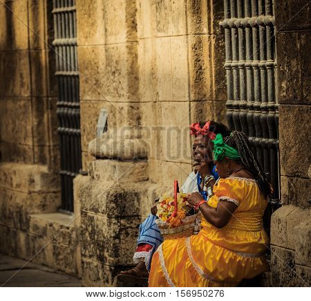 Havana, Cuba, Nov. 26, 2013, vintage retro dressed black women sitting near the old building wall illuminated with natural sunlight on old Havana street, relaxing and smoke cigars
