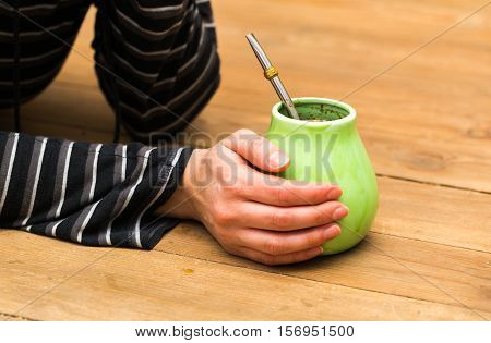 Unrecognizable woman drinking yerba mate from ceramic cup.