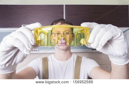 Man Hold Yellow Safety Glasses