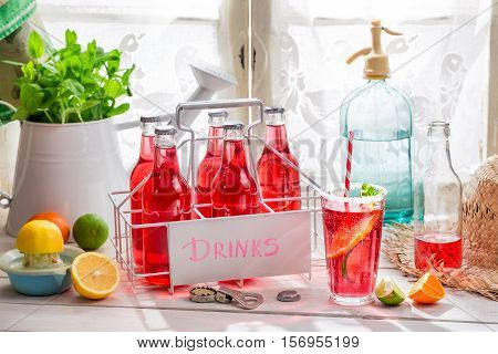 Tasty Red Orangeade In Bottle On Old White Table