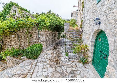 Small narrow street in Tucepi village in the slope of a mountain Biokovo.