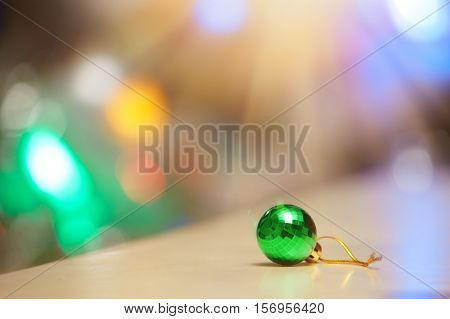 Green Christmas ball and illuminated background. Close-up view
