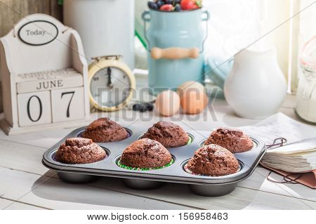 Decorating Tasty Muffins With Caster Sugar On Old White Table