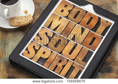 body, mind, soul and spirit - wellness concept - a word abstract in letterpress wood type on a digital tablet with cup of coffee