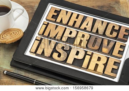 enhance, improve, inspire word abstract  - a collage of motivational words in vintage letterpress wood type on a digital tablet with a cup of coffee