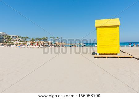 Xabia, Spain - September 7, 2016: Bright yellow changing shed stands out againgt white sand and blue sea and sky on Mediterranean beach Costa Blanca Blanca Xabia Spain