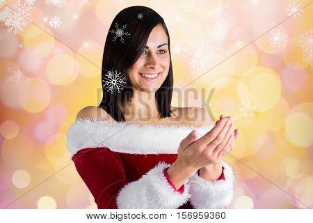 Beautiful woman in santa costume pretending to hold an imaginary snowflake