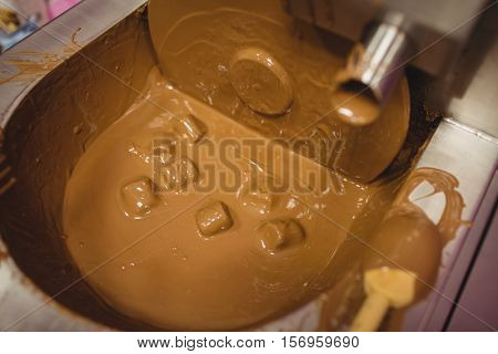 Close-up of marshmallow dipped in chocolate blending machine in kitchen