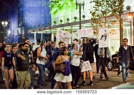 LOS ANGELES, CALIFORNIA - NOVEMBER 11, 2016: Protesters marching down the streets of downtown. Protesters holding signs,