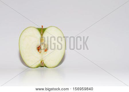 Green apple sliced in half on white background