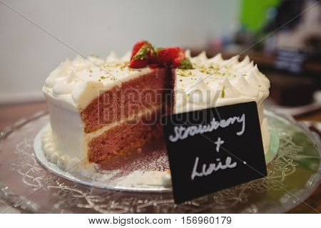 Close-up of strawberry cake on cakestand in cake shop