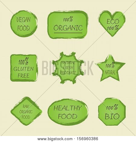 A set of green stickers with text Vegan 100% ECO Gluten Free Natural Fresh Product Raw Organic Product BIO Healthy Food. The background is painted with a brush.