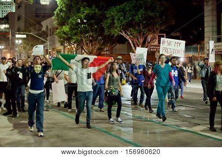 LOS ANGELES, CALIFORNIA - NOVEMBER 11, 2016: Protesters marching down the street of downtown. Protester holding sign,
