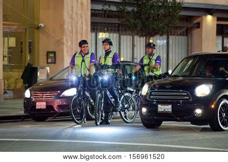 LOS ANGELES, CALIFORNIA - NOVEMBER 11, 2016: Three Purple Patrol, also known as The Safety and Clean Team officers on bicycles. Patrolling the Art District stopped at Red light.