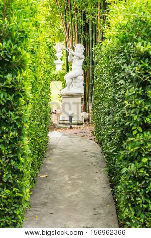 Beauty statue of Cupid in cozy garden on summer.
