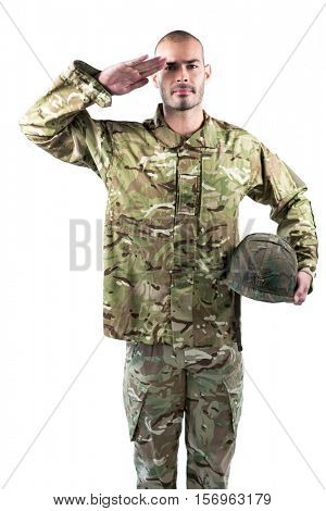 Portrait of confident soldier standing with a helmet and saluting against white background