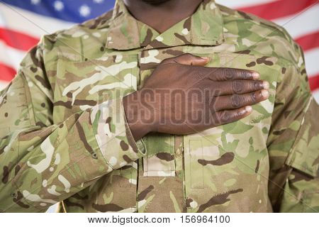 Mid section of soldier taking oath against american flag