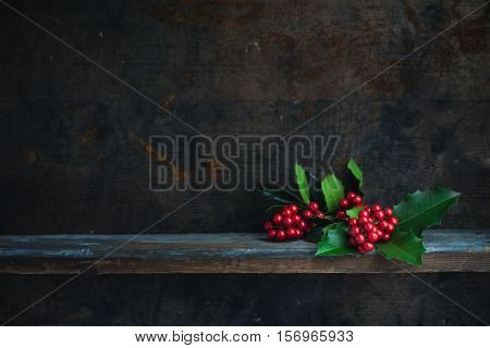Christmas Holly Twig. Christmas decoration with red berries placed on a wooden shelf.