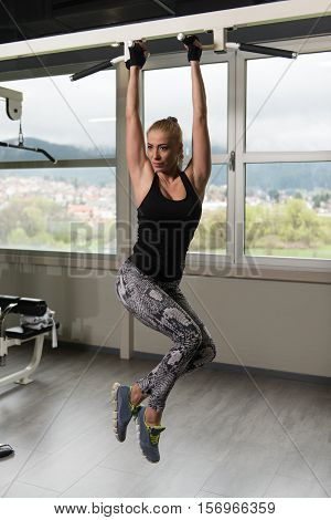Woman Performing Hanging Leg Raises Exercise