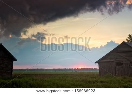 The dark clouds of the summer are gathering over the misty fields of the Northern Finland on a summer evening. The nights are getting warmer and the mist rises from the still cold ground.