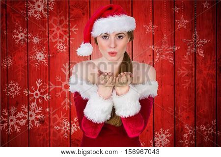 Woman in santa costume blowing a kiss against digitally generated red background