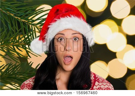 Portrait of shocked woman in santa hat during chirstmas time