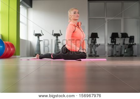 Healthy Woman Stretches At The Floor
