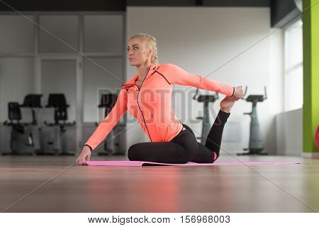 Fitness Woman Stretches At The Floor