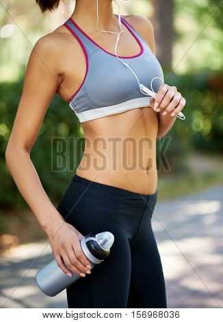 Female jogger in good shape listening to personal stereo and holding water bottle
