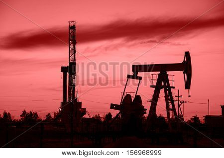 Oil pump jack and derrick silhouette during sunset in the oilfield. Oil and gas concept. Toned.
