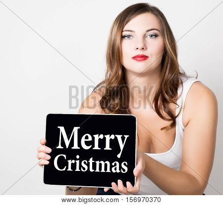 Merry cristmas written on virtual screen. technology, internet and networking concept. beautiful woman with bare shoulders holding pc tablet.