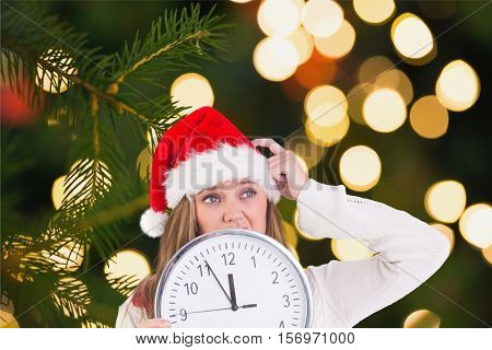 Thoughtful woman in santa hat holding a clock during christmas time