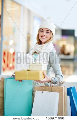 Beautiful girl posing with Christmas gifts in shopping center