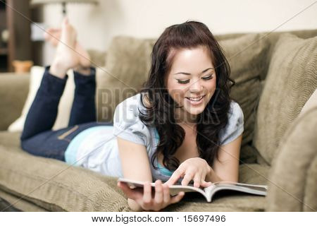Pretty young woman lounging on a couch with a magazine