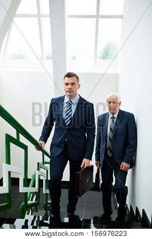 Business people walking up stairs in office building