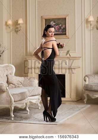 Portrait Of Woman In Interior.portrait Of A Woman In A Black Dress Beautiful Interio