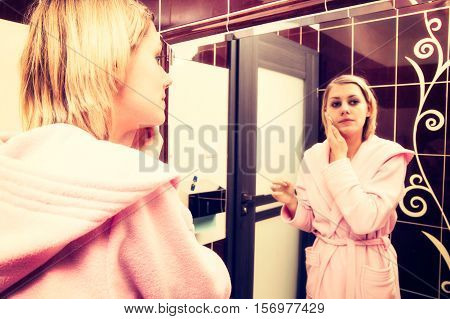 Blonde woman cleanse her face before make-up. Girl wearing in dressing-gown. Toned image