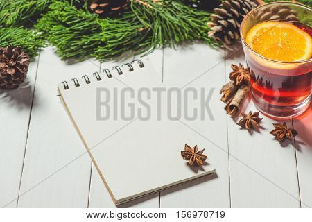 Christmas drink. Glass cup of tea with lemon and cinnamon with notebook on wood table